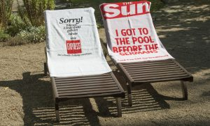 Two towels with English and German slogans on deckchairs